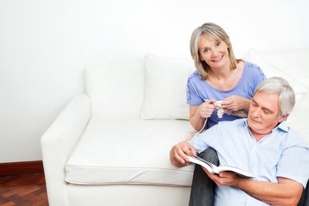 Senior couple sitting at home on couch and reading and knitting photo
