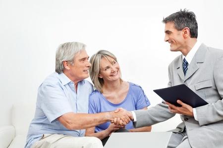 Handdruk tussen senior paar en de financiële adviseur
