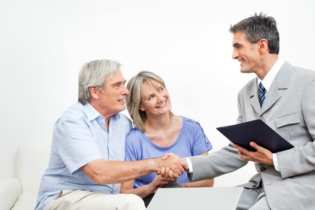 Handshake between senior couple and financial consultant photo