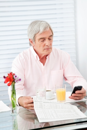Senior man with newspaper and cell phone at breakfast table photo