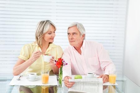 desayuno romantico: Matrimonios de edad en la mesa del desayuno con el caf� y el peri�dico Foto de archivo