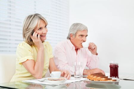 Senior woman using her cell phone at breakfast table photo