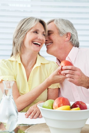 Senior couple in love flirting at breakfast table photo