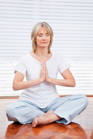 Relaxed senior woman meditating at home on floor photo