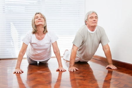 Two senior people doing yoga exercise Bhujangasana in gym photo