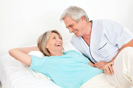 Senior couple laying laughing in bed in the bedroom Stock Photo - 12361455
