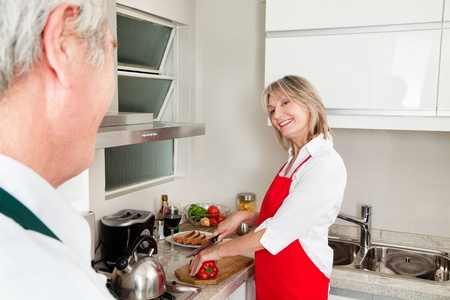 Smiling happy senior woman preparing dinner in kitchen photo