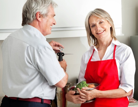 Happy senior couple cooking together in kitchen photo