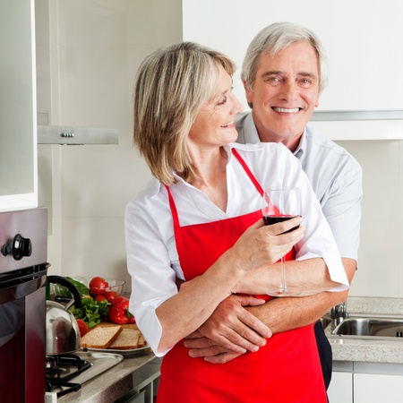 Happy senior husband embracing smiling wife in kitchen photo