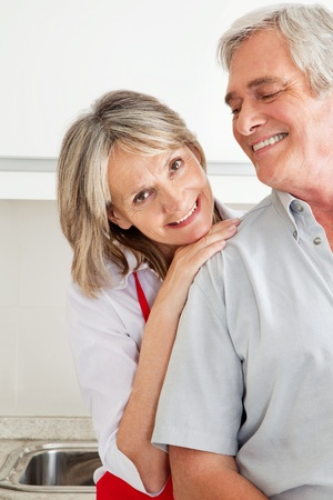 Senior woman in kitchen leaning on shoulder of man photo