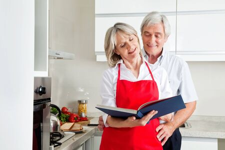 Happy senior couple in kitching looking for recipes in a cookbook photo