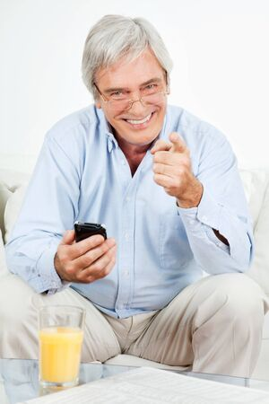 Smiling senior man with smartphone at home on couch Stock Photo