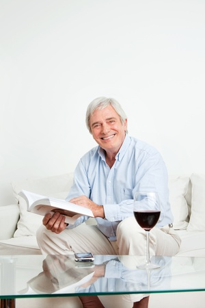 Happy senior man reading a bestseller book on couch photo
