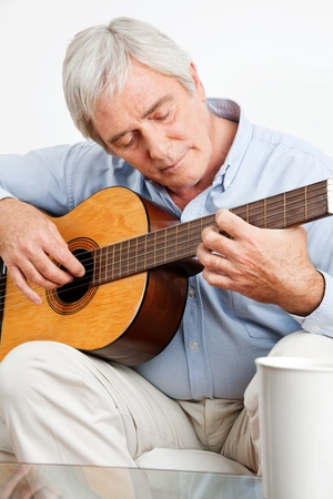 Elderly man on couch playing acoustic guitar photo