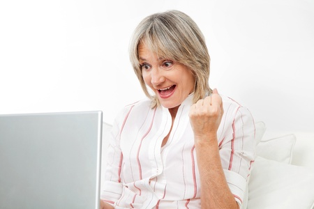 online bidding: Happy senior woman cheering while looking at computer