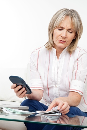 savings problems: Senior woman with many Euro money and calculator in living room Stock Photo