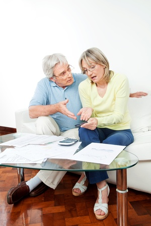 worry: Senior couple with paperwork fighting over money at home