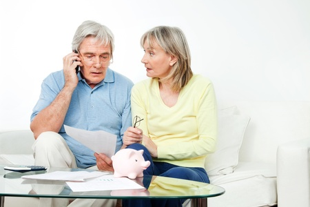 Senior couple in living room complaining on cell phone photo