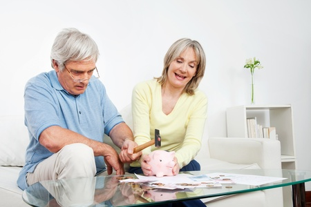 Senior couple breaking piggy bank with a hammer at home photo
