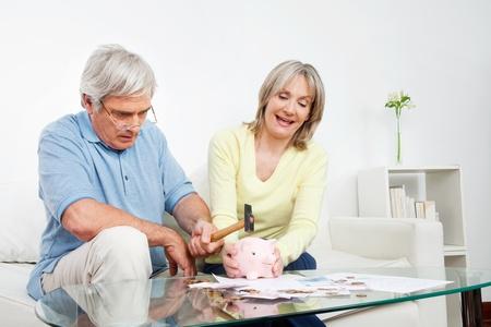 abastecimiento: Senior pareja romper la hucha con un martillo en su casa