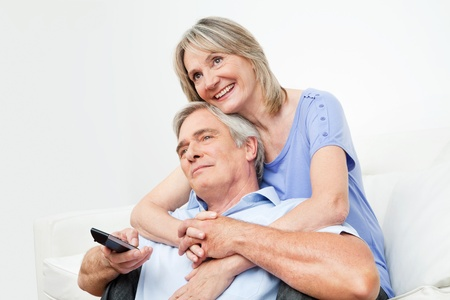 Senior couple watching TV together with remote control at home photo