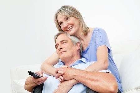 pareja viendo tv: Senior pareja viendo la televisi�n junto con el control remoto en el hogar