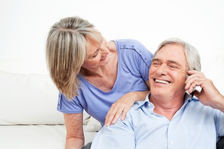 Happy senior couple talking in cell phone at home photo