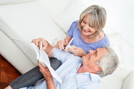 coziness: Man showing senior woman knitting patterns at home in a book