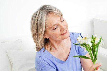 coziness: Happy senior woman with bouquet of white lilies flowers Stock Photo