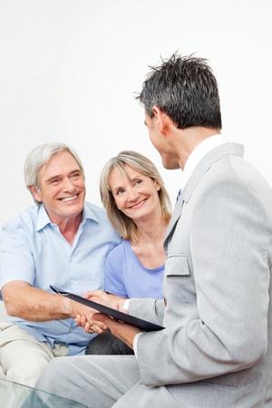 Senior paar begroeting financieel consultant bij handdruk thuis
