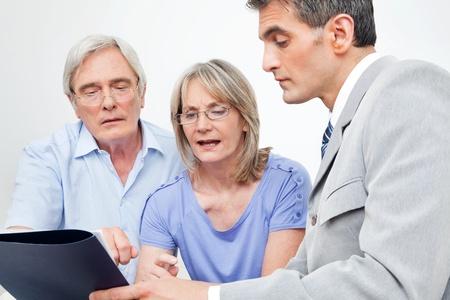 Senior paar krijgt financieel advies van consultant in huis