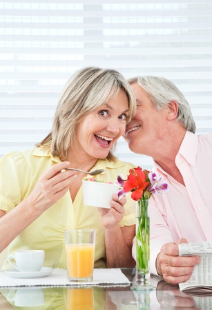 Senior man whispering secret into happy womans ear photo