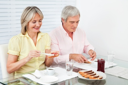 Married senior couple eating breakfast together with toast and jam photo