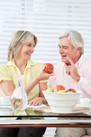 Senior couple having healthy breakfast with fruits and water photo