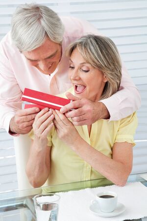 Senior man giving his surprised wife a gift photo