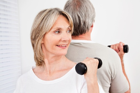 vital: Senior couple back to back in fitness class in gym