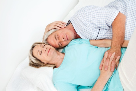 Senior couple sleeping relaxed together in bed photo
