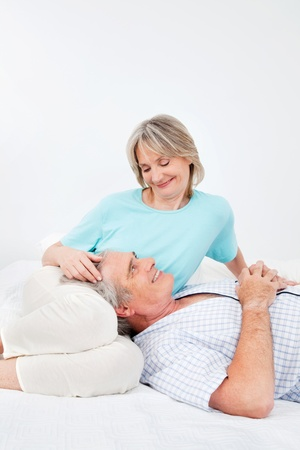 Senior man and woman relaxing together in bedroom Stock Photo - 12361490