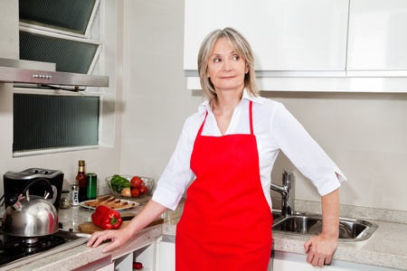 Senior woman with red apron standing in kitchen photo