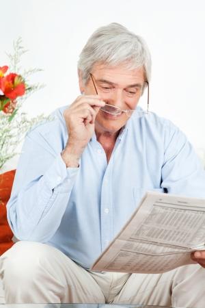 oude krant: Senior man met een bril lezen van een krant Stockfoto