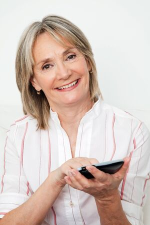 Happy senior woman using smartphone with touchscreen photo