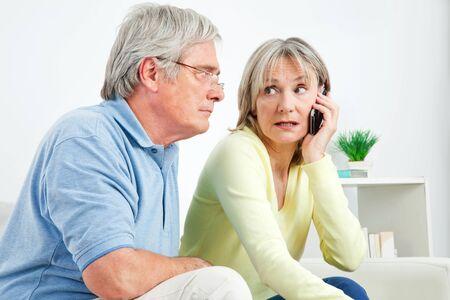 Starszy kobieta rozmawia przez telefon komórkowy w domu w salonie