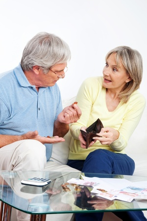 Elderly couple with empty wallet discussing financial issues at home