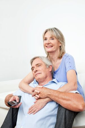 Happy senior couple watching TV at home with remote control photo