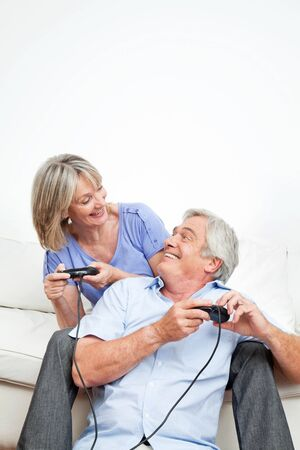 Two happy seniors playing computer games with game controller photo