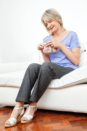 Happy senior woman knitting at home in living room photo