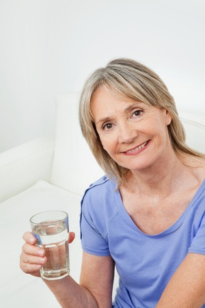 Smiling senior woman with glass of water at home photo