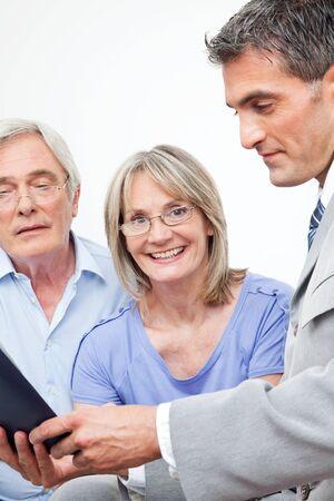Happy senior vrouw met haar man thuis met financieel adviseur