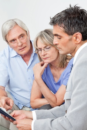 consultation woman: Financial advisor talking to senior couple at home
