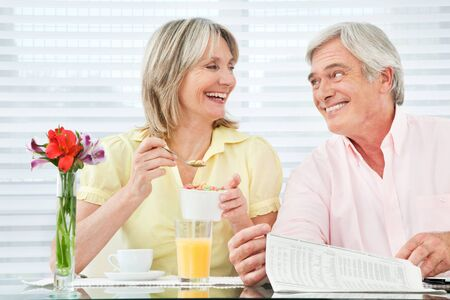 Happy smiling senior couple eating breakfast at home photo